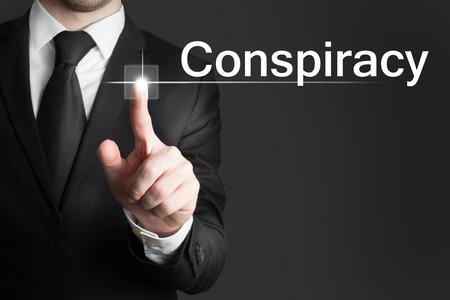 conspire: businessman pressing touchscreen button conspiracy