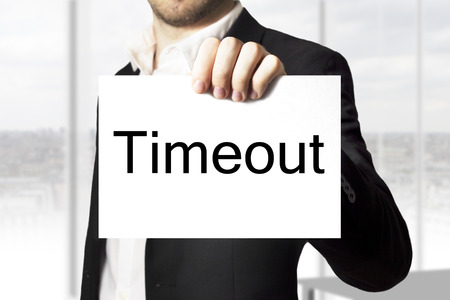 businessman in black suit holding white sign timeout photo