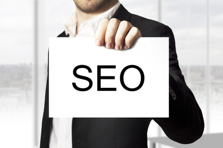web crawler: businessman in black suit holding white sign seo