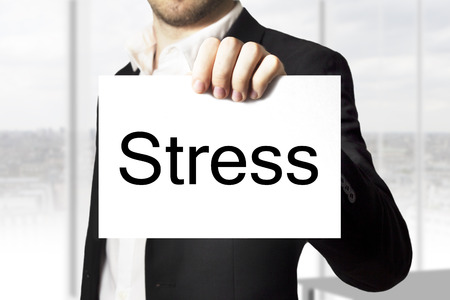 businessman in black suit holding white sign stress photo