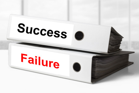 clumsiness: stack of two white office binders success failure Stock Photo