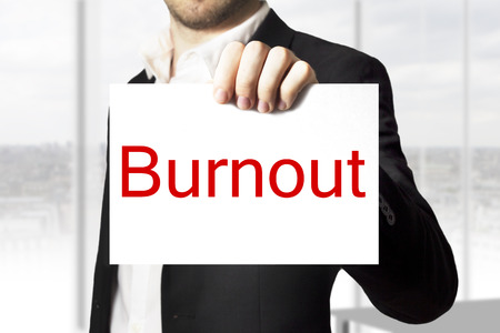 businessman in black suit holding sign burnout