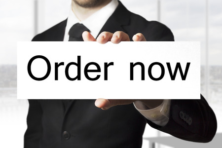 preorder: businessman in black suit holding sign order now Stock Photo