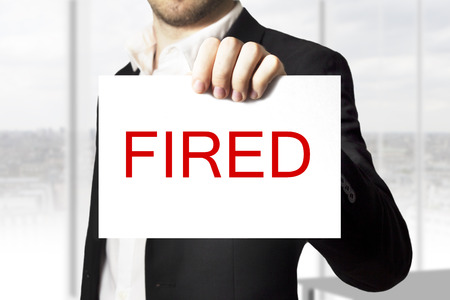 decission: businessman in black suit holding white sign fired Stock Photo