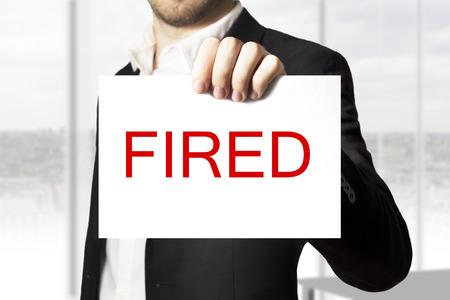 decission: uomo d'affari in vestito nero che tiene segno bianco sparato Archivio Fotografico
