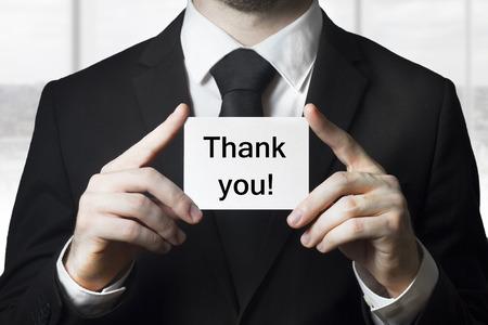 gratefulness: hombre de negocios en traje negro que sostiene la peque�a tarjeta blanca gracias Foto de archivo