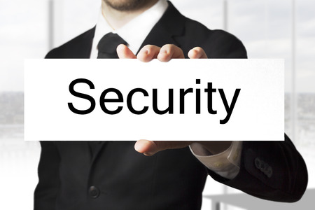 businessman in black suit holding sign security