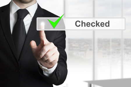 businessman in black suit pushing touchscreen checked green