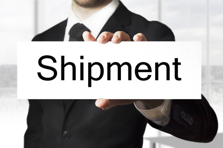 businessman in black suit holding sign shipment photo
