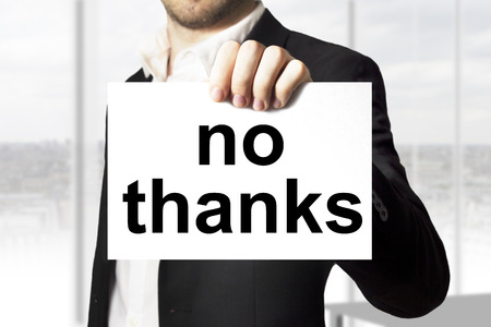 businessman in black suit holding sign no thanks Stockfoto