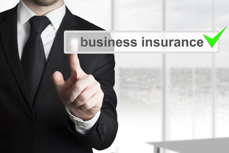 businessman in black suit pushing button business insurance photo