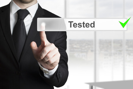 tested: businessman pushing touchscreen tested checked green