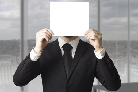 whistleblower: businessman in black suit hiding his face behind paper sign Stock Photo