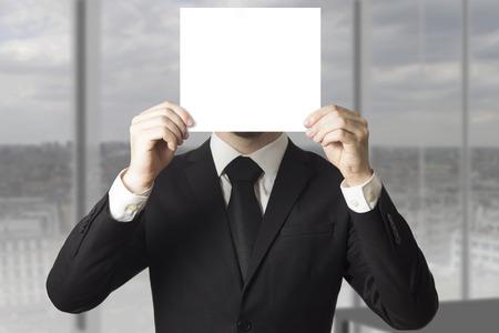 businessman in black suit hiding his face behind paper sign Standard-Bild