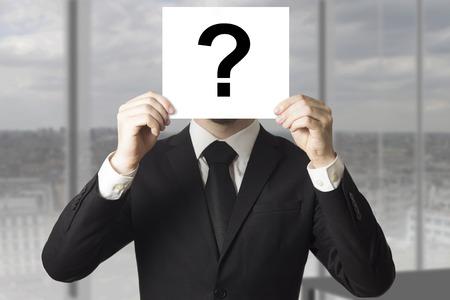 businessman in black suit hiding face behind sign question mark Standard-Bild