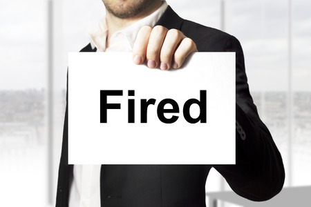decission: businessman in black suit holding sign fired