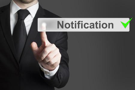 notification: businessman in black suit pushing button notification