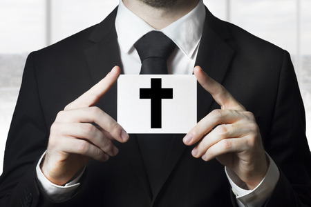 mortician: undertaker man in black suit holding sign black cross funeral Stock Photo