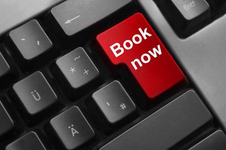 agencia de viajes: teclado oscuro libro botón rojo ahora los viajes de vacaciones Foto de archivo