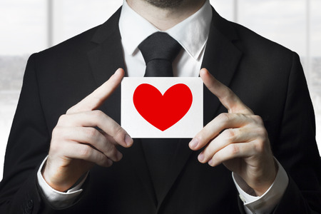businessman in black suit holding sign red heart symbol photo