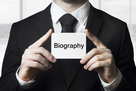 businessman in black suit holding sign biography