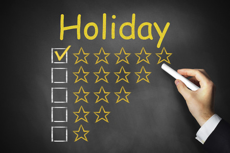 hand writing holiday on black chalkboard golden rating stars photo