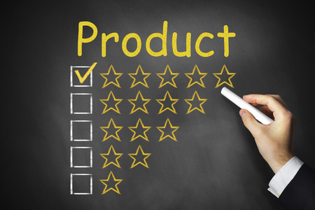 hand writing product rating golden rating stars on black chalkboard photo