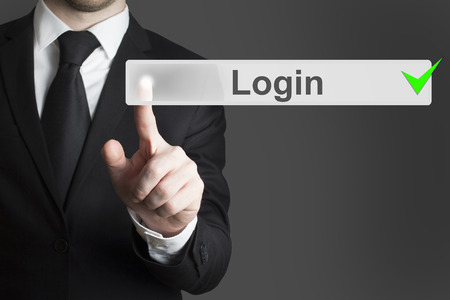 businessman pushing touchscreen button login green checked