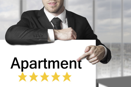 businessman in black suit pointing on sign apartment golden rating stars photo