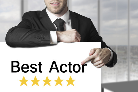 nominated: businessman in black suit pointing on sign best actor golden stars award