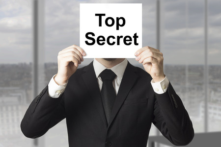 secret password: businessman in black suit hiding face behind sign top secret Stock Photo