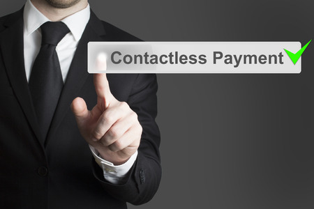 contactless: businessman in black suit pushing virtual button contactless payment checked Stock Photo