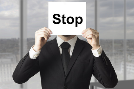 bad plan: businessman in black suit hiding face behind sign stop