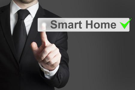 businessman in black suit pushing flat button smart home automation Standard-Bild