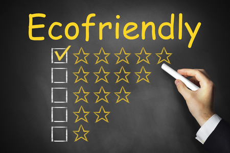 electricity providers: hand writing ecofriendly on black chalkboard golden star rating