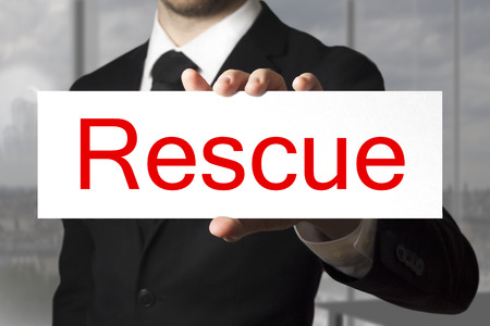businessman in black suit showing sign rescue photo