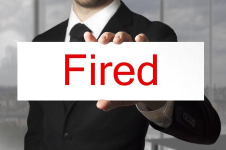 decission: uomo d'affari in abito nero segno di partecipazione licenziato