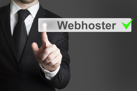 webhoster: businessman in black suit pushing flat button webhoster checked Stock Photo