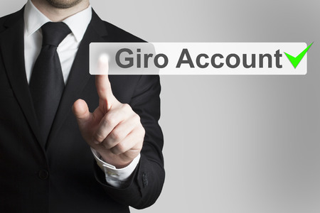 international bank account number: businessman in black suit pushing flat button giro account Stock Photo