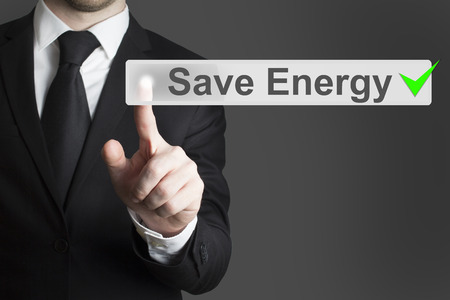 powerhouse: businessman in black suit pushing flat touchscreen button save energy eco mode Stock Photo
