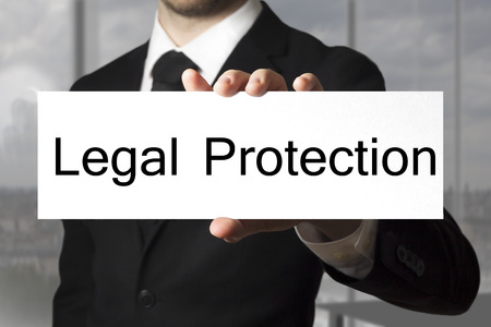 businessman in black suit office showing sign legal protection Archivio Fotografico