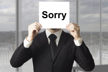 bad pardon: businessman in black suit hiding face behind sign sorry Stock Photo