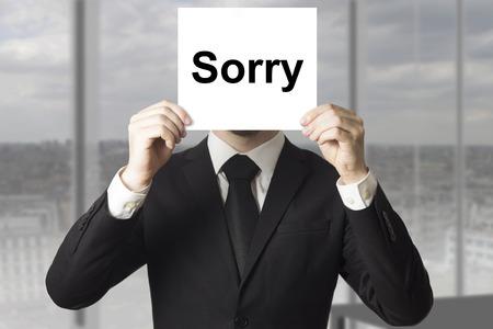 businessman in black suit hiding face behind sign sorry Standard-Bild
