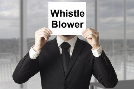 businessman in black suit hiding face behind sign whistle blower Standard-Bild