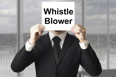 businessman in black suit hiding face behind sign whistle blower Stockfoto