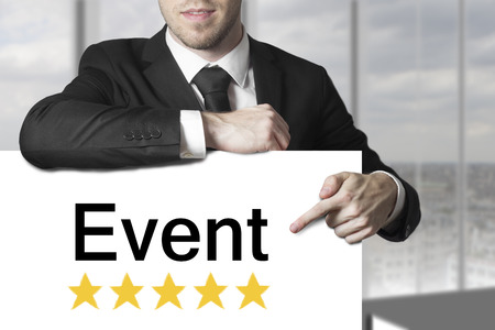 vod: businessman in black suit pointing on sign event golden stars rating