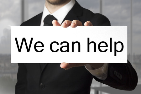 warranty questions: businessman in black suit showing sign we can help