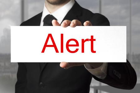 businessman in black suit holding sign alert photo