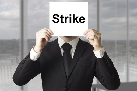 businessman in black suit hiding face behind sign strike photo