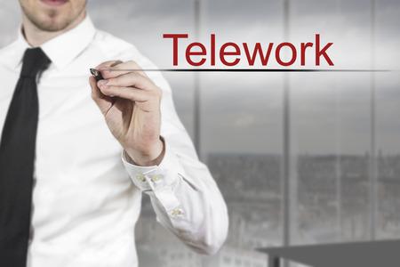 telework: businessman in office writing telework in the air